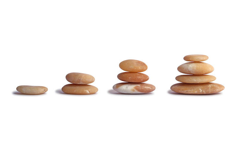 Stones stacked on white background, a symbol of growth, the concept of growth.
